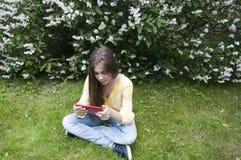 有片剂计算机的美丽的少年女孩坐草在公园 照片 免版税库存照片