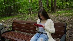 有片剂计算机的美丽的少年女孩坐长凳在公园 静态照相机电影与steadicam的 股票录像