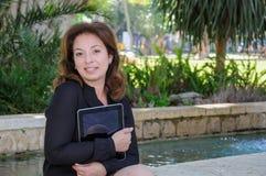 有片剂计算机的年轻女商人在公园长椅 库存照片