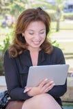 有片剂计算机的年轻女商人在公园长椅 免版税图库摄影