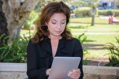 有片剂计算机的年轻女商人在公园长椅 免版税库存照片