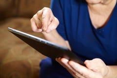 有片剂计算机的年长妇女 免版税库存照片