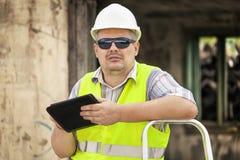 有片剂近倒塌的修造的房屋检查员 免版税库存照片