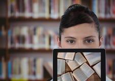 有片剂陈列开放书的妇女反对模糊的书架 库存图片