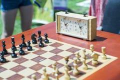 有片断的在木书桌上的棋盘和时钟与棋比赛相关 免版税库存图片