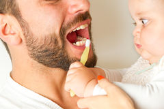 有牙刷掠过的牙的婴孩从父亲 免版税图库摄影