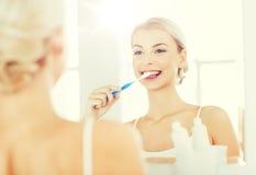 有牙刷清洁牙的妇女在卫生间 免版税图库摄影