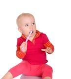 有牙刷的小女婴在白色背景 免版税图库摄影