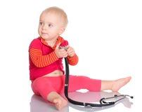 有牙刷的小女婴在白色背景 免版税库存照片