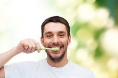 有牙刷的微笑的年轻人 免版税图库摄影