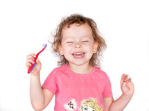 有牙刷的愉快的微笑女孩 库存照片