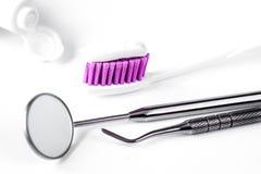 有牙医工具的牙齿保护牙刷在白色背景 免版税库存照片