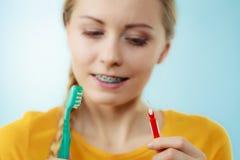 有牙括号的女孩使用牙齿之间和传统刷子 免版税库存照片