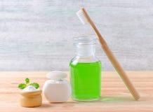 有牙膏木糖醇或苏打或盐和木头牙刷的,在木的牙线供选择的自然漱口瓶 库存照片