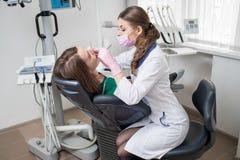 有牙齿工具的女性牙医-在牙齿诊所办公室反映并且探查对待耐心牙 免版税库存图片