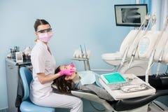 有牙齿工具的女性牙医-在牙齿诊所办公室反映并且探查检查耐心牙 库存照片