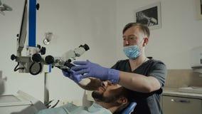 有牙齿工具的男性牙医在诊所-对待耐心牙的显微镜、镜子和探针在牙齿诊所办公室 影视素材