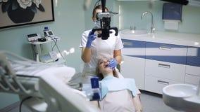 有牙齿工具的-对待耐心牙的显微镜、镜子和探针女性牙医在牙齿诊所办公室 医学 股票录像