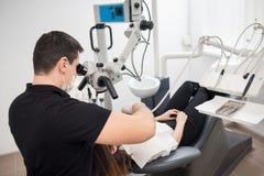 有牙齿工具的-对待耐心牙的显微镜、镜子和探针男性牙医在牙齿诊所办公室 库存照片