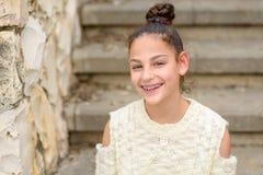 有牙齿括号的愉快的微笑的十几岁的女孩 免版税图库摄影