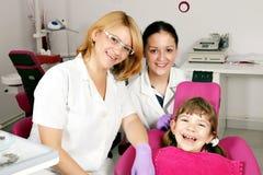 有牙医和护士的小女孩患者 免版税库存图片