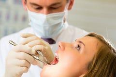 有牙医的-牙齿治疗患者 免版税库存照片