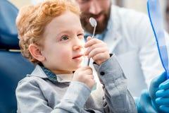 有牙医的男孩在牙齿办公室 免版税库存图片