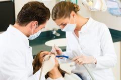 有牙医的-牙齿治疗患者 免版税库存图片