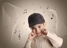 有牛仔布盖帽的音乐男孩 免版税图库摄影