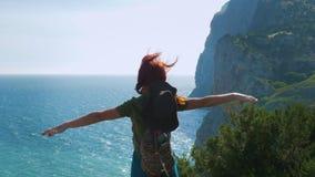 有牛仔帽和背包的一个年轻红发女孩旅客在山,被伸出的胳膊的上面站立 股票录像