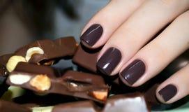 有牛奶巧克力片断的美好的妇女手  库存图片