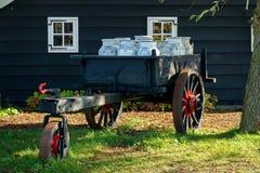 有牛奶店牛奶罐头的葡萄酒推车在传统老木房子前面 免版税库存照片
