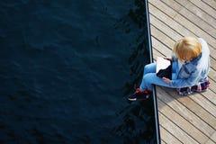 有牛仔布夹克的女孩,坐与他的腿摇晃码头的,当使用数字式片剂时 库存图片