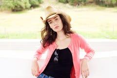 有牛仔帽常设外部的凉快的时尚妇女 免版税库存照片