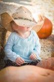 有牛仔帽的可爱的女婴在南瓜补丁 免版税图库摄影
