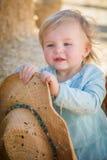 有牛仔帽的嬉戏的女婴在南瓜补丁 图库摄影
