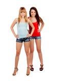 有牛仔裤短裤的两个青少年的姐妹 免版税库存照片