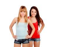 有牛仔裤短裤的两个青少年的姐妹 免版税库存图片