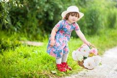 有牡丹和玫瑰篮子的小孩女孩  库存照片