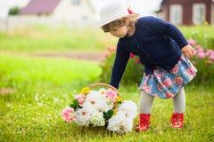 有牡丹和玫瑰篮子的逗人喜爱的小孩女孩  免版税库存照片