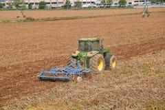 有犁土地的拖拉机的一位农夫在播种的073前 免版税库存照片