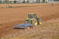 有犁土地的拖拉机的一位农夫在播种的073前 图库摄影