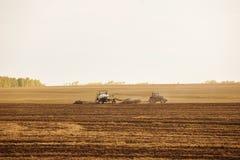 有犁播种的拖车的一台拖拉机领域农机为一片新的庄稼做准备 免版税库存图片