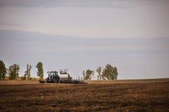 有犁播种的拖车的一台拖拉机领域农机为一片新的庄稼做准备 图库摄影