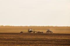 有犁播种的拖车的一台拖拉机领域农机为一片新的庄稼做准备 库存照片