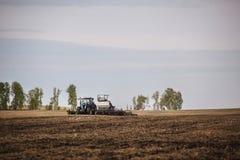 有犁播种的拖车的一台拖拉机领域农机为一片新的庄稼做准备 库存图片