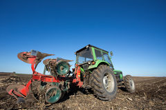 有犁的设备拖拉机在领域 免版税库存照片