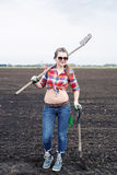 有犁耙和铁锹的妇女在领域 免版税库存照片