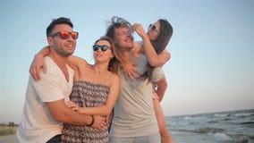 有狂放的暴牙的微笑的青年人一起花费时间的小组在海边上在刮风的天气和享用期间 影视素材