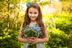 有狂放的蓝色花花束的女孩  免版税库存图片